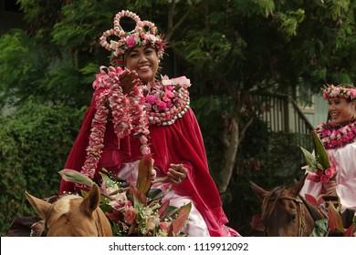 Lihue, Kauai, Hawaii / USA - June 9, 2018: The Princess of Maui representative in the King Kamehameha Day Floral Parade of Kauai poses with a traditional flower lei.