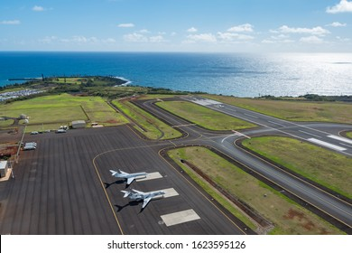Lihue, Kauai, HI USA 04/18/2019: Aerial helicopter view of the runway at Lihue Airport. Two small parked jets can be seen with the Pacific Ocean in the background.