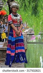 LIJIANG, CHINA - JUNE 11, 2015: girl in bright colorful costume is standing on the street in Lijiang, China