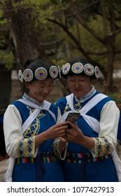 Lijiang, China - March 23, 2018: Chinese women wearing a traditional Bai minority attire using a smartphone in Lijiang, Yunnan