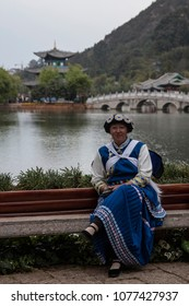 Lijiang, China - March 23, 2018: Chinese woman wearing a traditional Bai minority attire sitting in front of the Black Dragon Pool in Lijiang