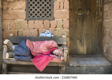 LIJIANG, CHINA - MAY 16: The unidentified person is sleeping on the street in the famous LiJiang Old City, China on May 16 2014. Lijiang is one of the biggest and well-preserved old town in China.