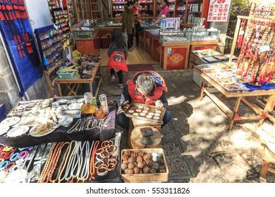 Lijiang, China - November 14, 2016: Young Naxi man working on his workshop in Lijiang Old Town