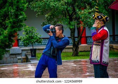Lijiang / China - Oct 2018: Chinese photografer make a photo of tourists in a traditional Yunnan dress in the Old Town of Lijiang. Old Town of Lijiang is a UNESCO World Heritage Site in Asia.