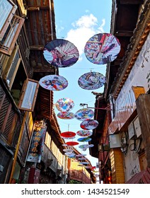 Lijiang City, Yunnan, China - 17 May, 2019: The old town of Lijiang is beautiful and historical. This picture is the alleys have hanging umbrellas above. Look so pretty under a sunlight and sky backgr
