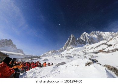 Lijiang City, Yunnan Province, China—March 13, 2018: Many tourists crowded to watch the snow dragon Snow Mountain spectacular scene, people looked up to the top