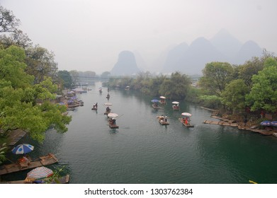 Lijiang River between Guilin and Yangshuo, China with boats cruising down the river with the misty karst mountains in the background.