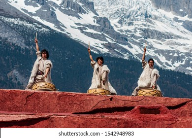 Lijiang, Yunnan, China - April 2 2012: The ethnic minority of the Naxi people in their traditional costumes; scene from a public perfomance with the Jade Dragon Snow Mountain in the background.