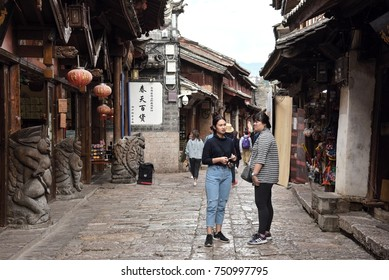 LIJIANG, YUNNAN, CHINA - OCTOBER 09, 2017: Unidentified tourists at old town of Lijiang in Yunnan. It was enlisted as a UNESCO World Heritage and is a main tourist site in China.