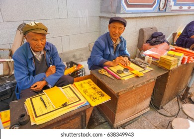 LIJIANG, YUNNAN/CHINA - JUNE 15: The Old man  Sits and writes Chinese on the roadside on June 15, 2016 in Lijiang City, Yunnan, China.