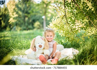 likable and Beautiful child play with doll dog in the summer. Green nature background