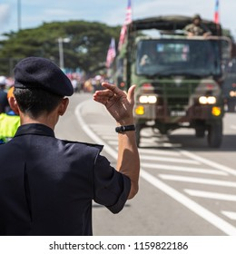 Likas, Kota Kinabalu, Sabah, Malaysia - August 31 2013: Police officer directing a military truck during the Parade on ocassion of the Celebrations of Hari Merdeka 2013 in Likas on August 31, 2013