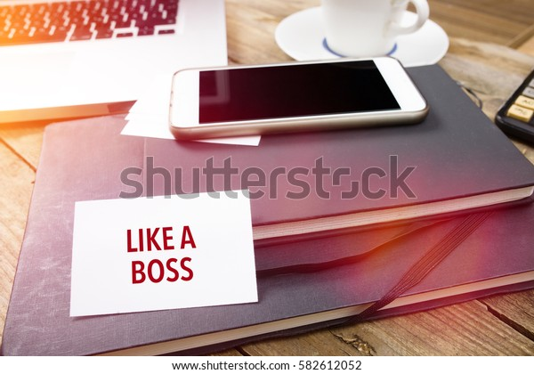Like A Boss on business card with text on office desktop with electronic devices, sun lit with lens flares.