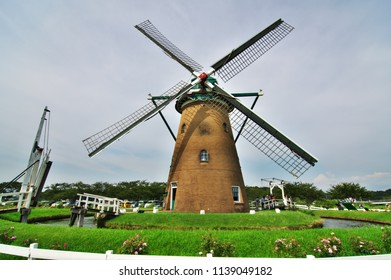It's like a colorful dutch landscape with a windmill and yellow sunflower field in view at  Sakura city, Chiba, Japan.