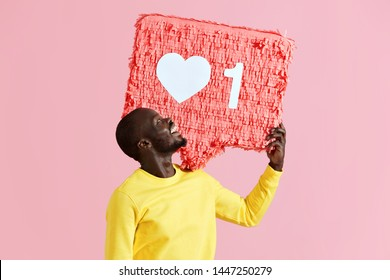 "Like. Happy black man holding like heart icon pinata on pink background. Smiling male model in yellow fashion clothes demonstrating ""like"" sign button, social media symbol"