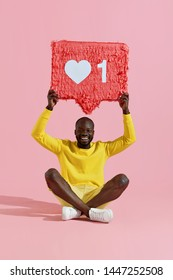 """Like. Happy black man holding like heart icon pinata on pink background. Smiling male model in yellow fashion clothes demonstrating """"like"""" sign button, social media symbol"""
