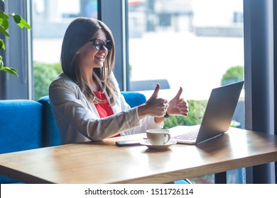 Like it. Portrait of happy satisfied beautiful stylish brunette young woman in glasses sitting, looking at her laptop screen, toothy smile and thumbs up. indoor studio shot, cafe, office background. - Shutterstock ID 1511726114