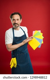 Like a magnet to dirt and dust. Household worker. Mature man holding colorful cleaning cloths. Eldery housekeeper presenting cleaning towels. Senior man in apron with rubber gloves. Household service.