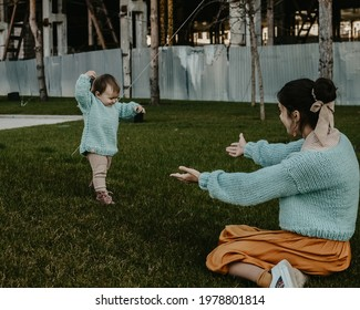 Like mother like daughter, mom and girl wearing turquoise sweaters playing on the grass in the park, mom waiting for her toddler baby girl to do her first steps