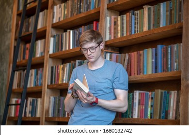Like to read. Young man in eyewear holding a book
