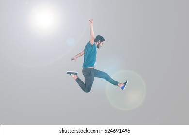 Like a rock star. Mid-air shot of handsome young man in cap jumping and gesturing against background