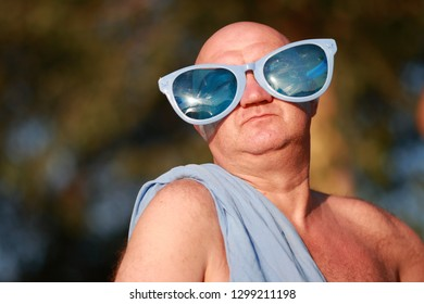 Like a roman patrician. Humorous portrait of an adult bald man in a blue toga and funny blue glasses. On the beach, relax.