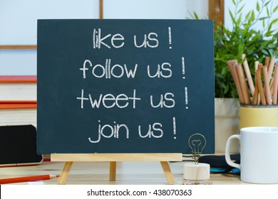 like us follow us tweet us join us- message text on a blackboard with pencils coffee cup and mobile phone. the concept of social media marketing and management