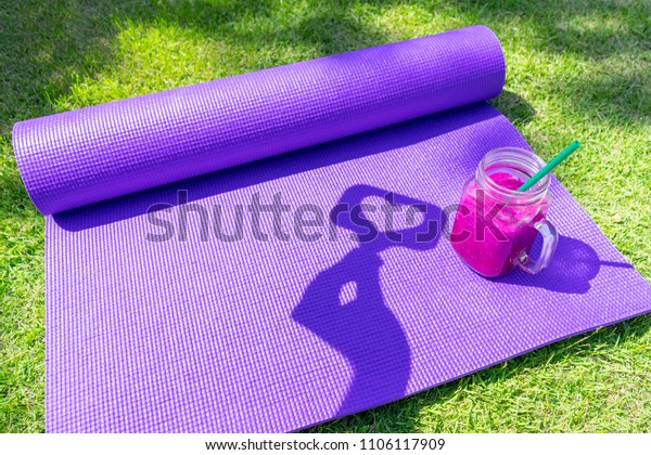 Like us shadow icon, dragon fruit purple milk shake and yoga mat on grass lawn like concept copy space