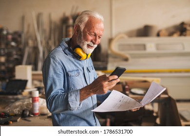 Likeable senior joiner is smiling while looking at the mobile phone. He is at his workplace holding a blueprint in the other hand