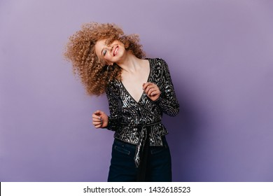 Likeable woman with shiny shadows dressed in shirt with silver sequins and dark pants dancing on purple background