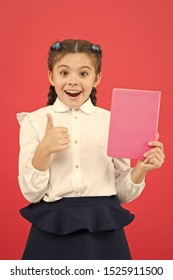 Liking her idea. Happy schoolgirl got main idea of book. Adorable little girl with book showing ok sign to bright idea. Small cute child smiling of genius idea, copy space.
