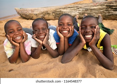 LIKOMA ISLAND, MALAWI - JUNE 17, 2018: Unidentified happy children relax on the beach in a village on Likoma Island. Malawi is one of the poorest countries in the world.