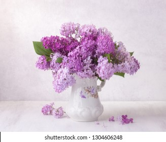 Lilac bouquet in the faience jug on a white wooden table.  Soft focus.
