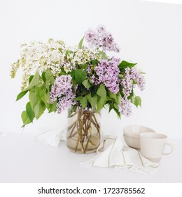 Lilac bouquet on a white table. Scandinavian minimalism. Flowers in the kitchen. Bouquet of lilac with utensils
