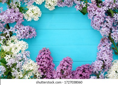 Lilac branches on a background of blue wooden boards. Floral romantic background with a copy space in the center. Frame of lilac flowers top view. The beginning of spring, Mother's Day holiday.