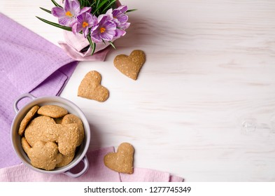 lilac crocuses and sesame dry cookies in the form of heart on a light wooden table