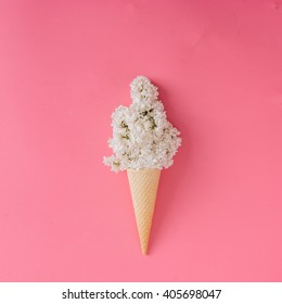 Lilac flower in ice cream cone on pink background. Minimal concept. Flat lay.
