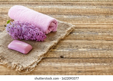 Lilac flower, soap and towel for bathroom procedures on sackcloth and wooden boards. Spa products and accessories. Top view.
