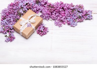 Lilac flowers and cute gift box on white wooden background, copy space. Mother's day background