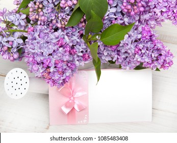 Lilac flowers and empty card on white wooden background, copy space