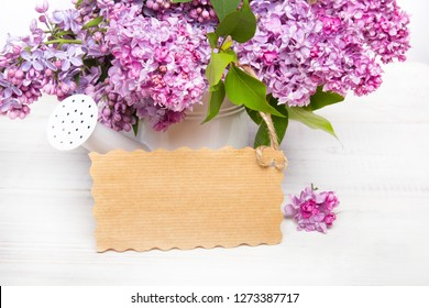 Lilac flowers and empyt card on white wooden background, copy space
