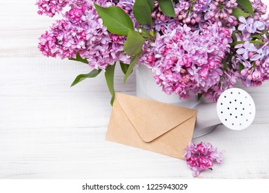 Lilac flowers and envelope on white wooden background, copy space