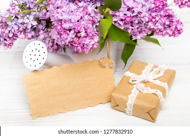 Lilac flowers, gift box and emty card on white wooden background, copy space