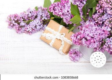 Lilac flowers and gift box on white wooden background, copy space