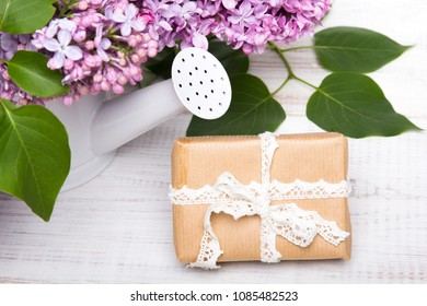 Lilac flowers, gift box on white wooden background