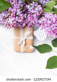 Lilac flowers and gift box on white wooden background