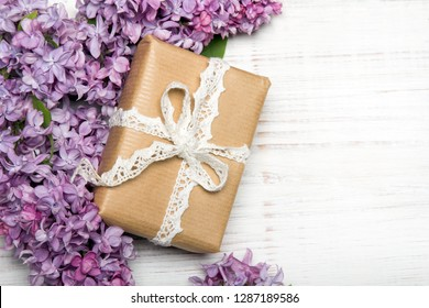 Lilac flowers, gift box on white wooden background, copy space