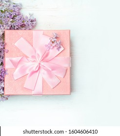 Lilac flowers and gift box on white wooden background. Spring season gift. Greeting card concept. Top view. Flat lay. copy space