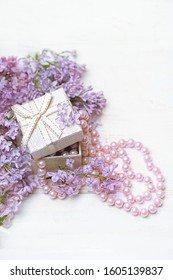 Lilac flowers and gift box with pearl beads on white wooden background. Spring season gift. Greeting card concept. copy space.
