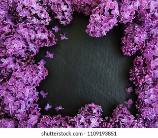 Lilac flowers on a black stone background